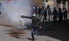 An Egyptian protestor throws away a tear gas canister