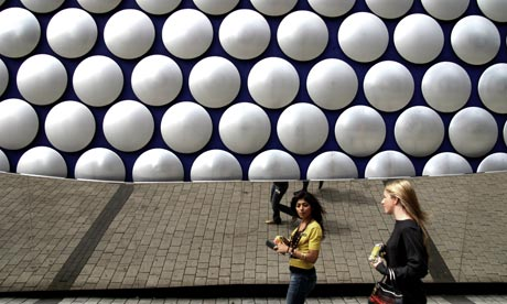 Young women walking past the distinctive Selfridges department store in the Bullring, Birmingham.