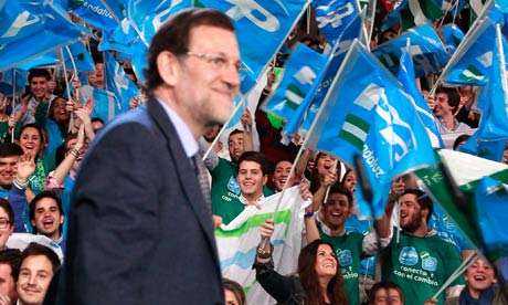 People's partys supporters wave flags as Mariano Rajoy arrives at a campaign rally in Seville