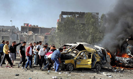 People help as cars burn at the scene of two suicides bombs in al-Qazar, Damascus