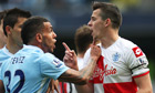 Queens Park Rangers' Joey Barton clashes with Manchester City's Carlos Tevez