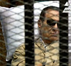 A screen grab from Egyptian state TV shows Hosni Mubarak sitting inside a cage in court