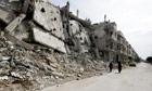 Syrian women walk past destruction in the Bab Amro