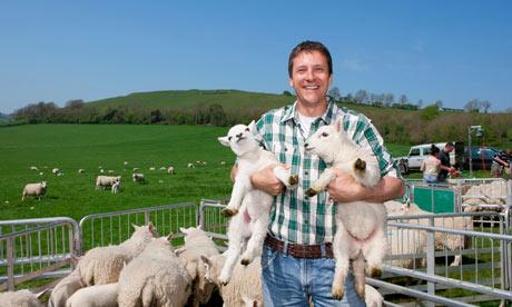 Portrait of smiling shepherd holding lambs in pasture
