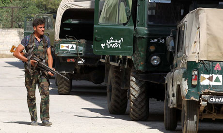 A member of the Free Syrian Army patrols a military base taken by rebels on the outskirts of Syria's second city, Aleppo. 