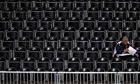 A lone man sits in an empty section of seats inside Earls Court during during a women's volleyball