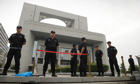 Police stand guard outside the court in Hefei where the Gu Kailai trial is being heard.