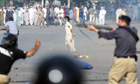 A demonstrator throws stones at police in Karachi.