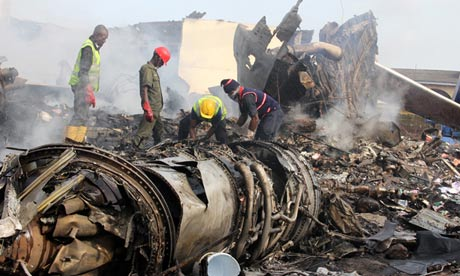 Firefighters work among the wreckage of the Dana Air plane that crashed in Lagos on 4 June 2012