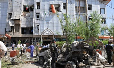 Iraqi security personnel inspect the site of a car bomb attack in Nassiriya