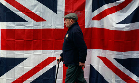 A man walks past a union flag  in west Belfast
