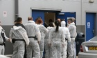 Immigration officials prepare to enter factory