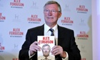 Alex Ferguson holding up his book
