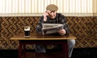 old man in pub reading newspaper, on phone