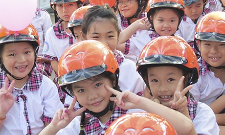 Vietnamese children wear motorcycle helmets