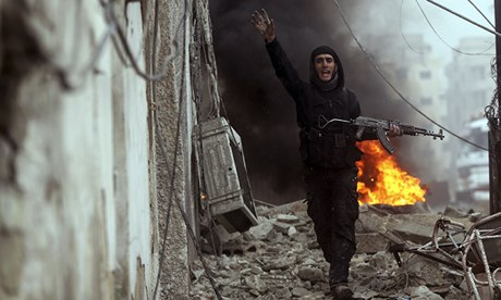 A Free Syrian Army fighter in front of a burning barricade in the Ain Tarma neighbourhood, Damascus