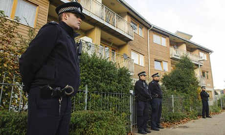 Police officers stand outside flats in Brixton
