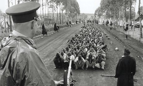 A colonial policeman and an auxiliary guard Mau Mau suspects in 1954. Photograph: Popperfoto
