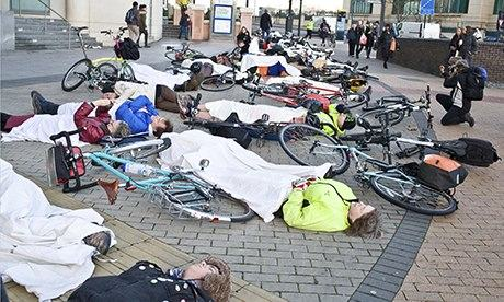 Cyclists lie down on the pavement at Vauxhall Bridge to protest about road safety.