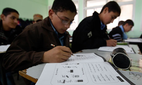 A Palestinian student writes during a Hebrew language class in a school in Gaza City