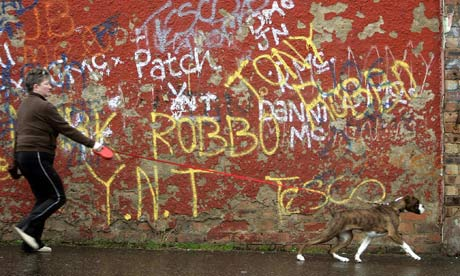 A woman walks her dog past graffiti