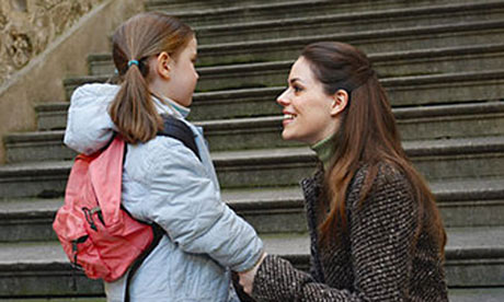 A mother drops her daughter off at school