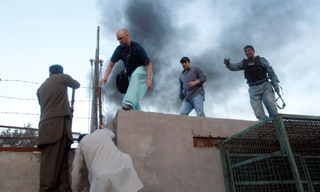 ICRC staff are helped to safety by police after the attack on their compound in Jalalabad.