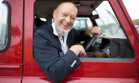 Glastonbury festival organiser Michael Eavis smiling at the wheel of a red Land Rover