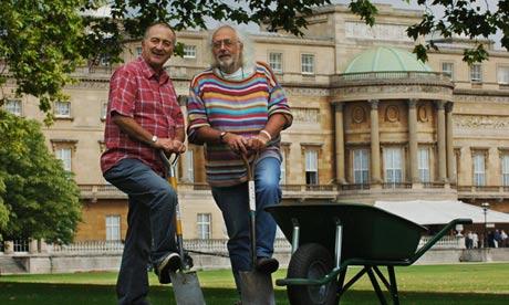 Mick Aston and Tony Robinson with spades outside Buckingham Palace
