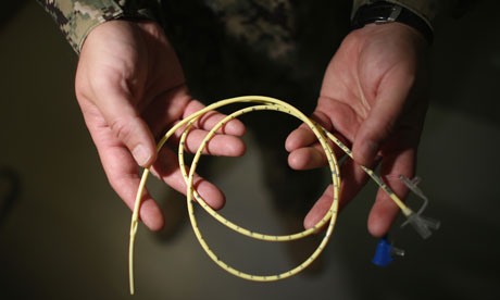 Doctor holds a tube used to force-feed hunger strikers at Guantánamo Bay
