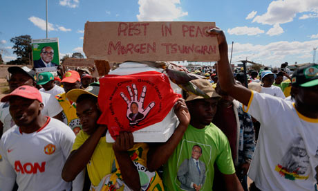 Supporters of Zimbabwe's president, Robert Mugabe, and Zanu-PF hold a coffin as they act out a fake funeral for Morgan Tsvangirai and his MDC-T party.