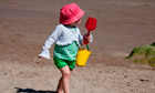 Little girl on the beach with yellow bucket