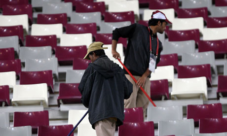 Asian workers cleaning the stadium at the end of the 2011 Asian Cup semi-final