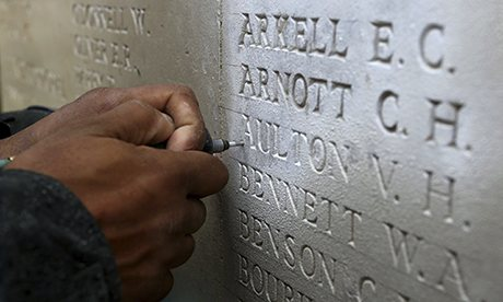 A stone mason restores names listed on a war memorial