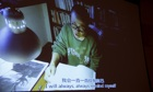 Liu Xia seated at a desk reads from one of her poems