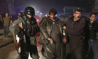 Police assist injured man at site of bombing in Kabul