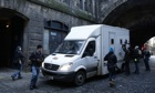 Photographers take pictures of a security van as it approaches Edinburgh sheriff court
