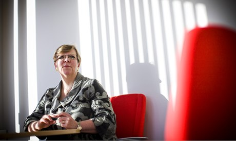 Alison Saunders pictured on a red chair with the reflection of venetian blind on wall behind her