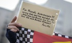 A fan holds a greetings card for Michael Schumacher