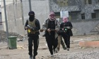 Al-Qaida gunmen patrol during clashes with Iraqi security forces in Falluja on Sunday,.