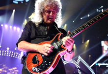 Brian May on stage playing guitar