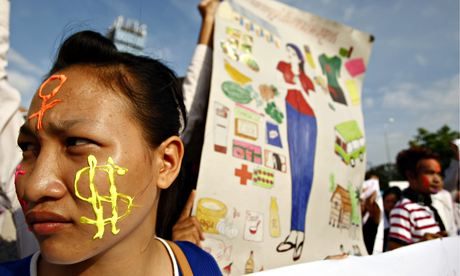 Cambodian garment factory worker with face painted with US dollar sign at a demonstration
