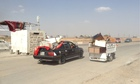 Cars loaded with goods drive away.Looters at K1 Iraqi army base near the city of Kirkuk