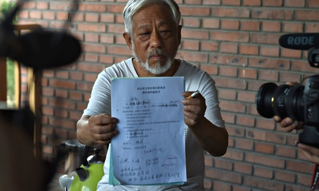 Li Xianting, Beijing independent film festival organiser, holds document up to the cameras
