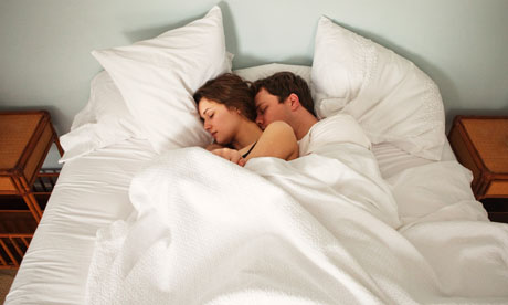 Couple lie in bed holding each other