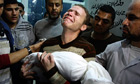 Jihad Masharawi weeps holding the body of his 11-month old son after Israeli air strikes on Gaza