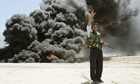 An Iraqi policeman shouts instructions at the scene following an attack on an oil pipeline