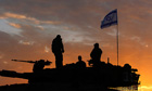 Israeli soldiers prepare to leave their Gaza border position as the ceasefire took hold.