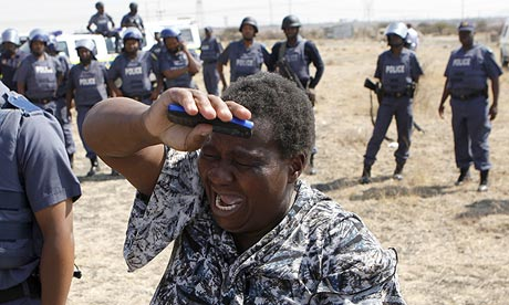 A woman cries as she confronts police at a protest over the killing of 34 miners at the Lonmin mine