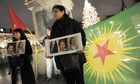 Kurds at a demonstration in Strasbourg hold photos of three Kurdish activists shot dead in Paris.